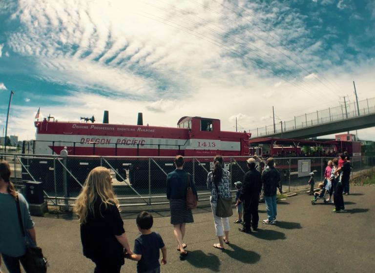 ポートランドにあるオレゴン レイル ヘリテイジ センター(ORHF)で子供と本物のディーゼル機関車に乗るため待っている人たち